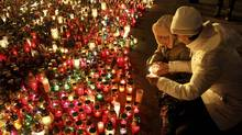 A woman lights candles to pay her respects to anti-government protesters in Lviv on Feb. 24, 2014. (MARIAN STRILSIV/REUTERS)