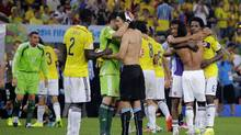 Colombia players greet Uruguay's Edinson Cavani, centre, after the World Cup round of 16 soccer match between Colombia and Uruguay at the Maracana Stadium in Rio de Janeiro, Brazil, Saturday, June 28, 2014. (Sergei Grits/AP)