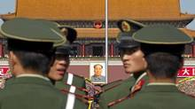 Paramilitary policemen look back while patrolling on the Tiananmen Sqaure in front of the late communist leader Mao Zedong's portrait in Beijing, China, Friday, Oct. 15, 2010. (Alexander F. Yuan/The Associated Press/Alexander F. Yuan/The Associated Press)