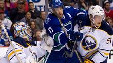 Vancouver Canucks' Ryan Kesler, centre, is checked by Buffalo Sabres' Tyler Myers, right, in front of goalie Ryan Miller during the first period of an NHL hockey game in Vancouver, B.C., on Saturday March 3, 2012. THE CANADIAN PRESS/Darryl Dyck (Darryl Dyck/CP)