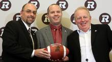 Ottawa RedBlacks general manager Marcel Desjardins, left to right, Rick Campbell and owner Jeff Hunt pose for pictures after it was announced Campbell will become the first coach for the new Ottawa RedBlacks CFL football team at a press conference in Ottawa, Friday December 6, 2013. (The Canadian Press)
