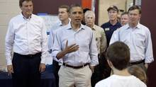President Barack Obama, flanked by Colorado Springs Mayor Steve Bach, left, and Colorado Gov. John Hickenlooper, right, speaks to volunteers and evacuees at the YMCA serving as an evacuation centre in Colorado Springs, Colo. (Carolyn Kaster/AP)