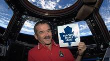 Chris Hadfield holds the logo of his favourite team, the Toronto Maple Leafs (Handout)