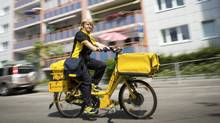 Iris Marossek of Deutsche Post, the German mail service, delivers mail using an e-bike. The e-bike's appeal seems largely limited to countries with a strong bike culture, surging in popularity in China, Germany and Netherlands, while the United States has yet to significantly embrace the new trend. (GORDON WELTERS/NYT)