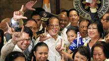 Philippine President Benigno (Noynoy) Aquino III, centre, flashes a laban, or 'fight' sign with a group of visitors at the presidential palace. (ROMEO RANOCO/REUTERS)