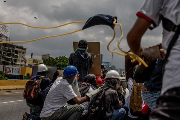 Protesters use an improvised slingshot to attack Venezuelan security forces during a protest against Venezuelan president Nicolas Maduro.