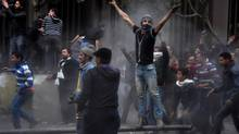 Egyptian protesters try to tear down a cement wall built to prevent them from reaching parliament near Tahrir Square, in Cairo, on Jan. 24, 2013. Egypt's black-clad riot police fired tear gas in fierce dawn clashes with dozens of protesters. (Hussein Tallal/AP)