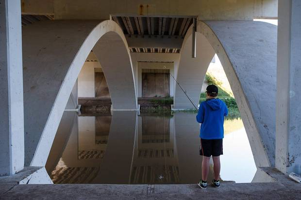 Aug. 24, 2016: Brasil Robalo, 11, fishes under an overpass as water levels of the North Saskatchewan River rise in Edmonton.