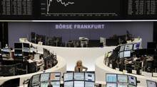 Traders work at their desks in front of the DAX board at the Frankfurt stock exchange May 10, 2013. (STRINGER/GERMANY/REUTERS)