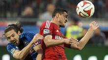 Toronto FC's Gilberto, right, heads the ball past Montreal Impact's Heath Pearce, left, during first half final Amway Canadian Championship soccer action in Toronto on Wednesday, May 28, 2014. (The Canadian Press)