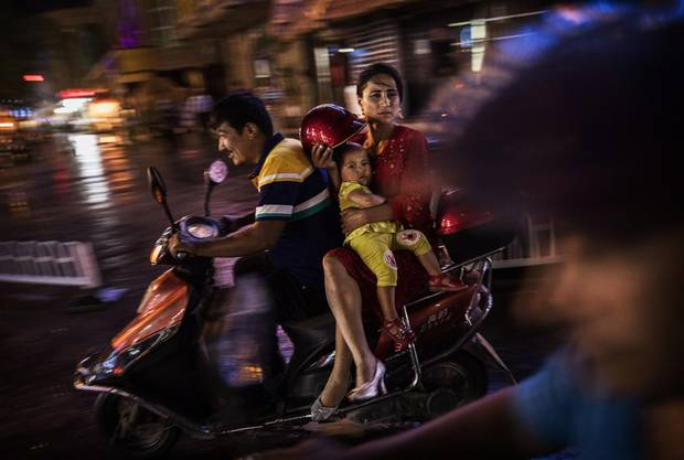 An ethnic Uyghur family ride a scooter on June 28, 2017 in the old town of Kashgar, in the far western Xinjiang province, China.