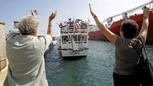 "People wave as ""The Audacity of Hope"", a U.S. boat which is part of a small flotilla which includes boats from the U.S, France and Canada, sails in Perama port near Athens, July 1, 2011. (John Kolesidis/Reuters/John Kolesidis/Reuters)"
