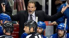 Vancouver Canucks' head coach John Tortorella, top, argues with referee Steve Kozari, 40, and linesman Vaughan Rody, 73, during second period NHL hockey action against the Los Angeles Kings in Vancouver, B.C., on Monday November 25, 2013. (The Canadian Press)