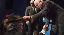 Barrck Gold's Chairman and Founder Peter Munk (right) places his trademark hat on the head of John Thornton after he attended the mining company's announcement of their first quarter results in Toronto on Wednesday April 24, 2013. (Chris Young/THE CANADIAN PRESS)