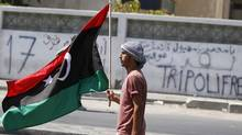 A Libyan rebel fighter carries the Kingdom of Libya flag in Tripoli August 23, 2011. (ZOHRA BENSEMRA/REUTERS)