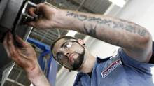 In this July 6, 2011 photo, technician Chris Shannon works on a costumers car at a Pep Boys Auto retail and service location, in Philadelphia. (Matt Rourke/AP)