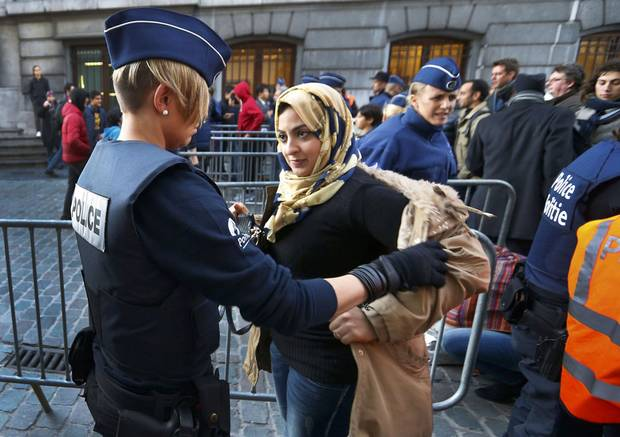 Residents of the Brussels suburb of Molenbeek are searched by police before taking part in a memorial gathering to honour the victims of the recent deadly Paris attacks, in Brussels, Belgium, November 18, 2015.