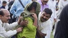 A Pakistani police official and a Christian volunteer escort a young Christian girl accused of blasphemy, towards a helicopter following her release from central prison on the outskirts of Rawalpindi, Pakistan on Saturday, Sept. 8, 2012. (Anjum Naveed/AP)