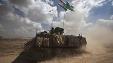 Israeli soldiers ride an armoured personnel carrier outside the Gaza Strip on July 15, 2014. (NIR ELIAS/REUTERS)