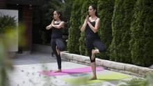 Grace Fusillo-Lombardi, 40, right, and her daughter Allessandra, 16, wear Lululemon pants while practising yoga poses at their home in Toronto. Grace and her daughter are Lululemon fans and have witnessed embarrassing situations with see-through yoga pants. The Vancouver-based high-end active wear retailer began restocking in June after recalling 17 per cent of its women's bottoms last March. (Philip Cheung for The Globe and Mail)