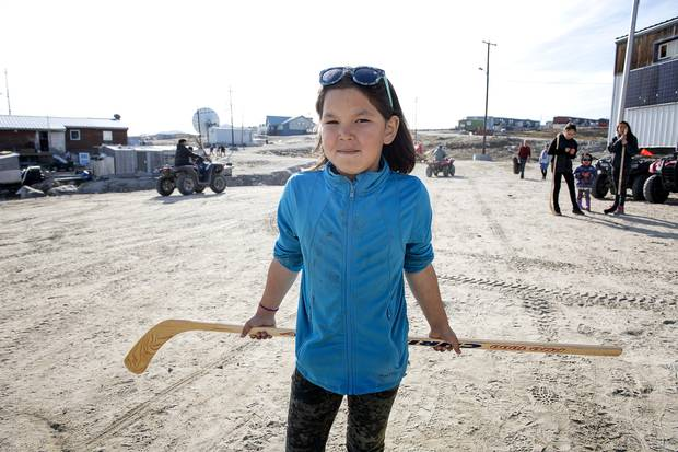 A resident of Clyde River holds her ball hockey stick, a much-debated gift from the southerners on the Polar Prince. Michelle Valberg/Students on Ice Foundation.