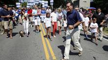 U.S. Republican presidential candidate and former Massachusetts Governor Mitt Romney crosses the street as he takes part in the Wolfeboro Fourth of July Parade in Wolfeboro, New Hampshire July 4, 2012. (JESSICA RINALDI/Reuters)