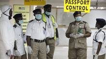 Nigeria health officials wait to screen passengers at the arrival hall of Murtala Muhammed International Airport in Lagos on Aug. 4, 2014. (SUNDAY ALAMBA/ASSOCIATED PRESS)