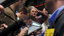 Traders of crude oil and natural gas react during early trading at the New York Mercantile Exchange on Friday. The economic fallout from a massive earthquake that struck off the east coast of Japan dipped oil below $100 for the first time this month. (Bebeto Matthews/Bebeto Matthews/AP)