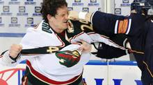 This Jan. 30, 2009, file photo shows Minnesota Wild left wing Derek Boogaard (24) getting hit by Edmonton Oilers left wing Steve MacIntyre (33) in a fight during first period NHL hockey action in Edmonton, Alta. Boogaard died of a drug overdose last year and a recent investigation has found he manipulated the NHL's medical system. (Jimmy Jeong/THE CANADIAN PRESS)