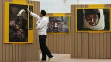 A man touches a photo as he visits a photographic exhibition of National Geographic Society in Gijon, Spain, July 19, 2007. (ELOY ALONSO/REUTERS)