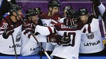 Latvia forward Lauris Darzins is congratulated by teammates after scoring against Switzerland in the third period of a men's ice hockey game at the 2014 Winter Olympics, Tuesday, Feb. 18, 2014, in Sochi, Russia. (Julio Cortez/AP)