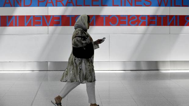 A passenger walks past Blue Republic's Delightful and Permanent Conditions of Impossibility, an installation art piece on display in Terminal 1 at Pearson International Airport, a part of Lumi