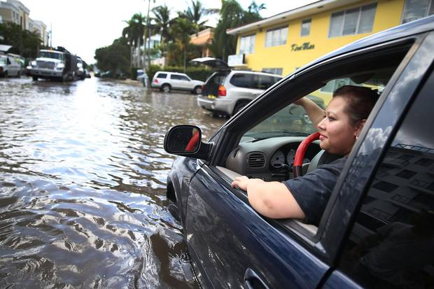 Sandy Garcia sits in her vehicle in Fort Lauderdale, Fla., that was stuck in a flooded street on Sept. 30, 2015.