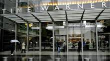 People walk in front of the Time Warner Inc. building in New York in a file photo. Time Warner is considering selling its New York headquarters and has asked real estate brokers to evaluate the building's value, according to sources. (STAFF/Reuters)