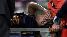 Barcelona's Carles Puyol is carried on a stretcher after injuring his arm in a fall during their Champions League group G soccer match with Benfica Tuesday, Oct. 2 2012, at Benfica's Luz stadium in Lisbon. (Armando Franca/AP)