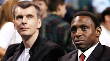 New Jersey Nets new owner Mikhail Prokhorov, left, sits with his new head coach Avery Johnson during Game 5 of the 2010 NBA Finals basketball series in Boston. (MIKE SEGAR)