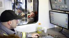 Trican Well Service employees monitor the hydraulic fracturing process from an onsite control centre near Bowden, Alta. (Jeff McIntosh/Jeff McIntosh for The Globe and Mail)