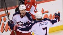 Columbus Blue Jackets' R.J. Umberger, left, celebrates a second period goal with teammate Jack Johnson as Ottawa Senators' Erik Condra skates past during NHL hockey action in Ottawa on Sunday, Nov. 17, 2013. (THE CANADIAN PRESS)