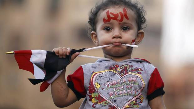 "A girl with the colours of the Egyptian flag and the word ""leave"" painted on her face is seen during a demonstration against Egyptian President Mohammed Morsi in front of the Presidential Palace ""Qasr Al Quba"" in Cairo on July 2, 2013. (AMR ABDALLAH DALSH/REUTERS)"