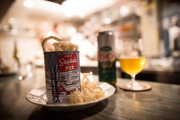 Deep-fried pork rinds are served tossed in maple syrup and Montreal steak spice and come flowing over the lip of a maple-syrup tin can at St. Lawrence.