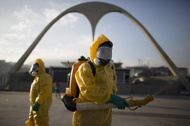 In this Tuesday, Jan. 26, 2016, file photo, health workers spray insecticide to combat the Aedes aegypti mosquito that transmits the Zika virus in Rio de Janeiro, Brazil.