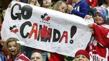 Team Canada fans cheer during the 86th Spengler Cup ice hockey tournament match against HC Davos, in Davos, Switzerland, Thursday, Dec. 27, 2012. (Salvatore Di Nolfi/AP)