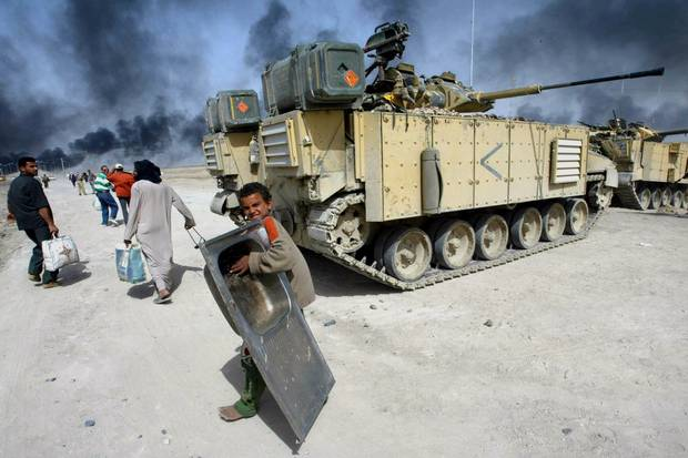 A Iraqi child carrying a sink passes a British tank as they flee Basra, southern Iraq, on March 29, 2003.