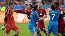 Toronto FC's Jonathan Osorio pushes Philadelphia Union goalie Chris Konopka, left, during first half MLS soccer game action in Toronto Saturday June 1, 2013. (Aaron Vincent Elkaim/THE CANADIAN PRESS)