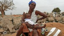 A pregnant Angolan mother is seen with one of her five children on the southern edge of Luanda in August, 2009. (LOUISE REDVERS/AFP/Getty Images)