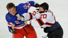 New Jersey Devils' Ryan Carter, right, fights with New York Rangers' Stu Bickel after the opening faceoff, March 19, 2012, at Madison Square Garden. (Bill Kostroun/The Associated Press/Bill Kostroun/The Associated Press)