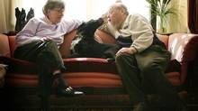 Farley Mowat gets a loving lick from his loyal companion, Chester, as his wife, Claire, looks on, in the couple's living room in Port Hope, Ont. (Charla Jones/The Globe and Mail)