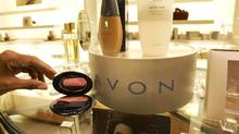 In this file photo, a saleswoman, who did not give her name, places items for a picture on display in an Avon store in New York. (Gregory Bull/AP)