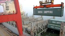 A shipping container is lifted by a crane at a port in Lianyungang, Jiangsu province April 10, 2014. (CHINA DAILY/REUTERS)