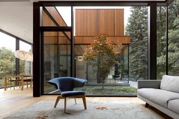 The living room, dining room and kitchen wrap around a small courtyard animated by a Japanese maple. The architects won a 2017 Ontario Wood Works Award for the design.